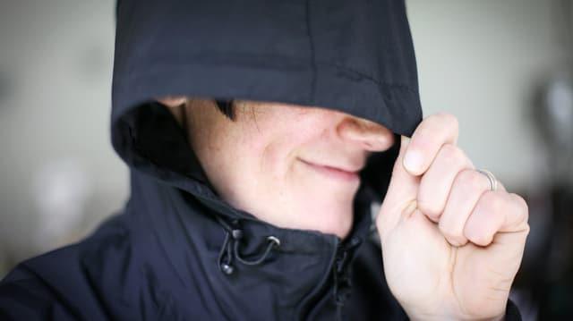 Eine Frau zieht ihre Kapuze über das Gesicht.