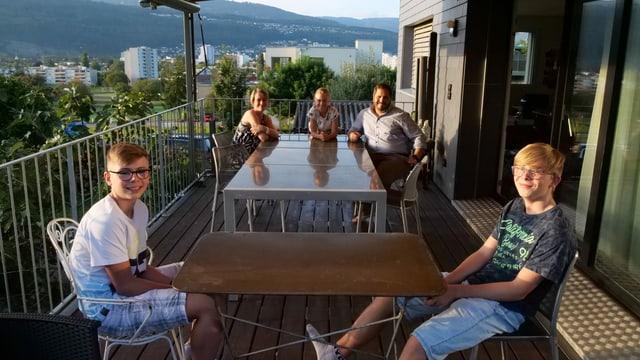 Alle sitzen auf der Terrasse. Die Buben an einem separaten Tisch.