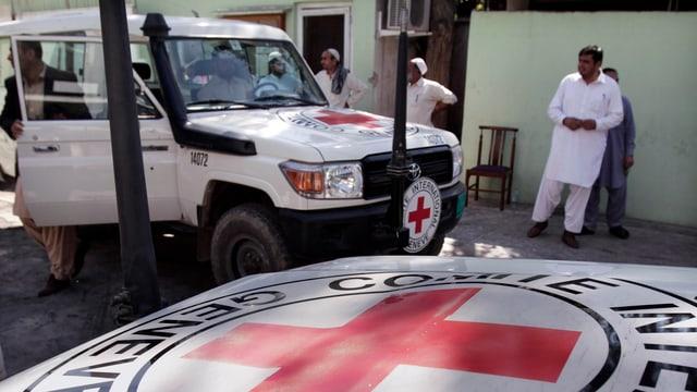 Ein weisser Jeep mit dem roten IKRK-Logo steht vor einem Haus in Afghanistan.