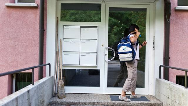 Spitexmitarbeiterin betritt ein Mehrfamilienhaus.