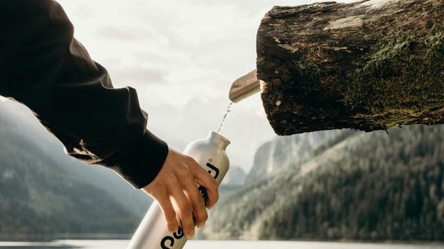 eine Flasche wird  an einem Brunnen mit Wasser aufgefüllt
