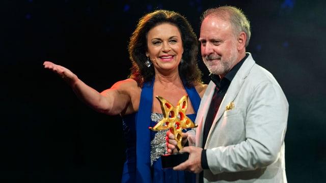 Monika Kälin im blauen Kleid mit Peter Reber im hellen Anzug, der die Trophäe in den Händen hält.