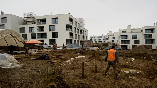 Arbeiter auf einer Baustelle in einem Wohnquartier.