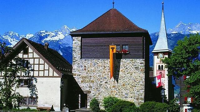 Turm des Tellmuseums in Bürglen, daneben ein Kirchturm, im Hintergrund schneebedeckte Alpengipfel.