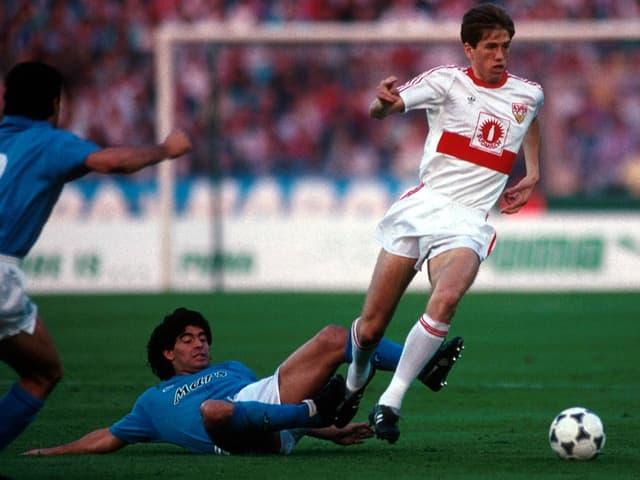 Maradona rutscht am Boden hinter Katanec her.