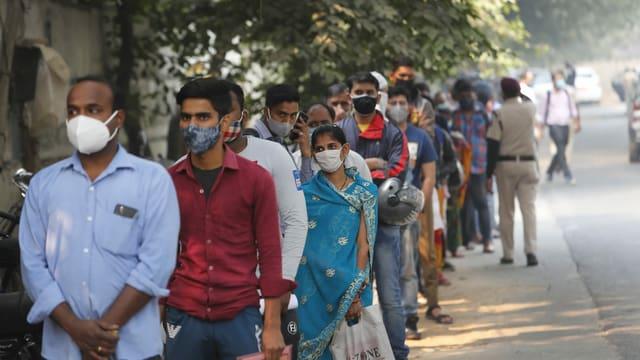Menschen mit Masken warten in einer langen Schlange auf ihren Coronatest.