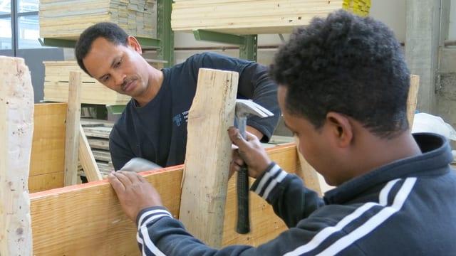 Zwei Männer arbeiten an Holzteilen.