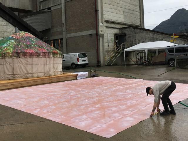 Eine grosse rote Blache wird vor der Zementfabrik ausgebreitet.