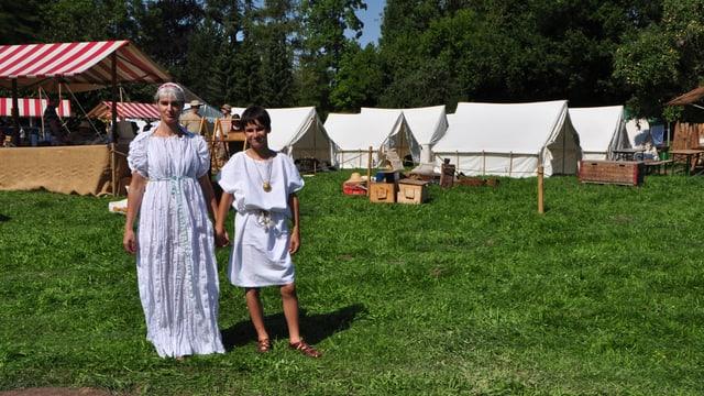 Frau und junges Mädchen in Römerkleidung, weisse Tuniken und Ledersandalen. Im Hintergrund die weissen Zelte des Römerfests.