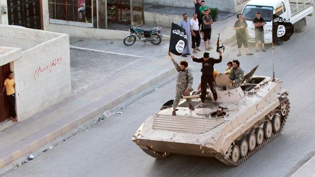 Junge Dschihadisten stehen auf einem rollenden Panzer und schwingen eine IS-Fahne.