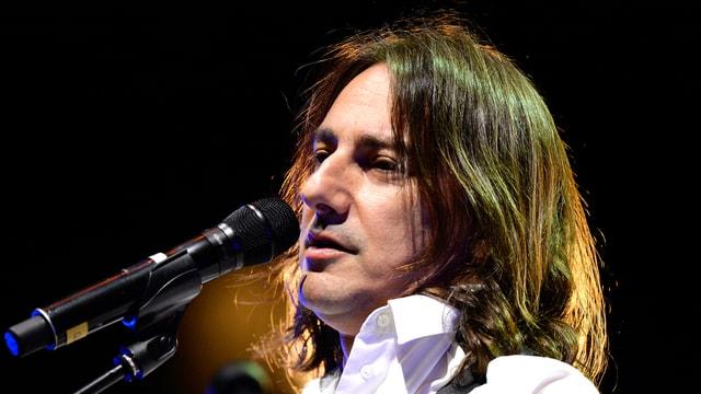 Pippo Pollina vor dem Mikrofon, Gitarrenband um den Hals, er trägt ein weisses Hemd und lange braune Haare.