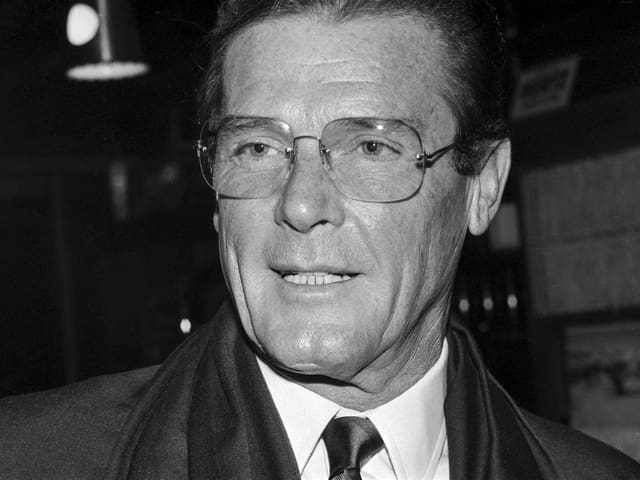 Roger Moore im Anzug mit Brille.