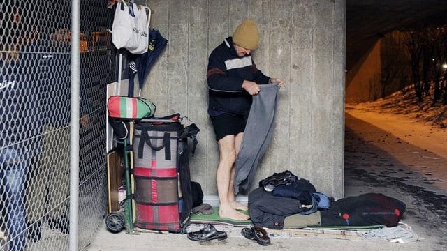 Ein Mann bereitet sein Bett unter einer Brücke in Zürich vor.