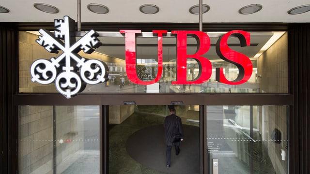 Il logo da l'UBS avant ina porta d'ina filiala da banca.