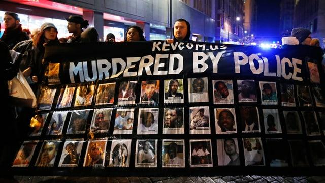 Eine Person hält ein Plakat mit Opferbildern.