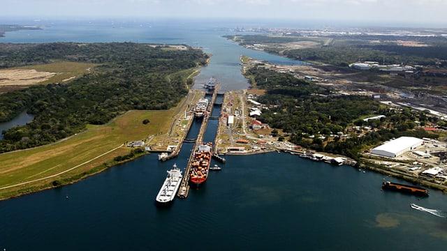 Ein Kanal mit Schiffen, die den Kanal gerade verlassen; links und rechts Land.