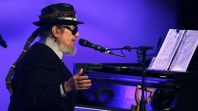 Musiker Dr. John sitzt am Klavier und spielt ein Konzert.