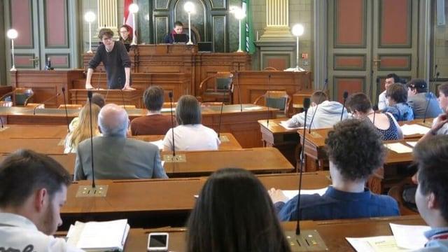 Jugendliche sitzen auf den Stühlen der St. Galler Grossräte und diskutieren.