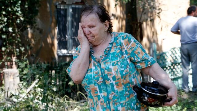 Frau mit einem Kochtopf unter dem Arm, sie weint.