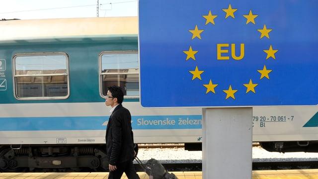 Ein Mann geht an einem Schild mit dem EU-Logo entlang, im Hintergrund ein Zug.