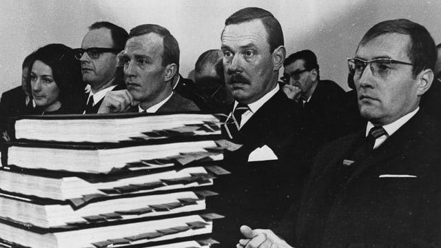 Schwarz-weiss-Foto: Männer hinter einem Stapel Bücher.
