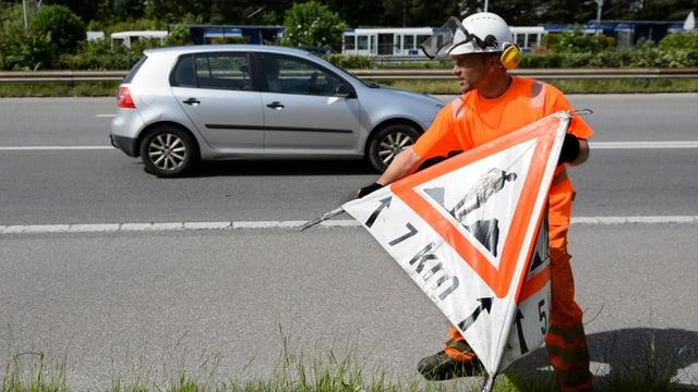 Strassenbauarbeiter mit Warnschild