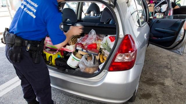 Ein Grenzwächter durchsucht einen mit Lebensmitteln gefüllten Kofferraum.