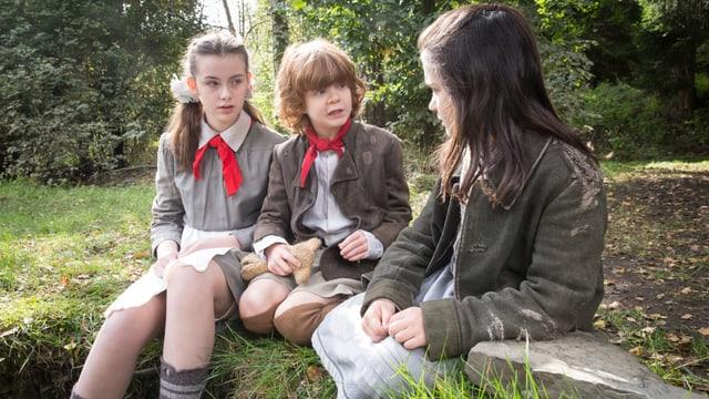 Drei Waisenkinder sitzen im Wald.