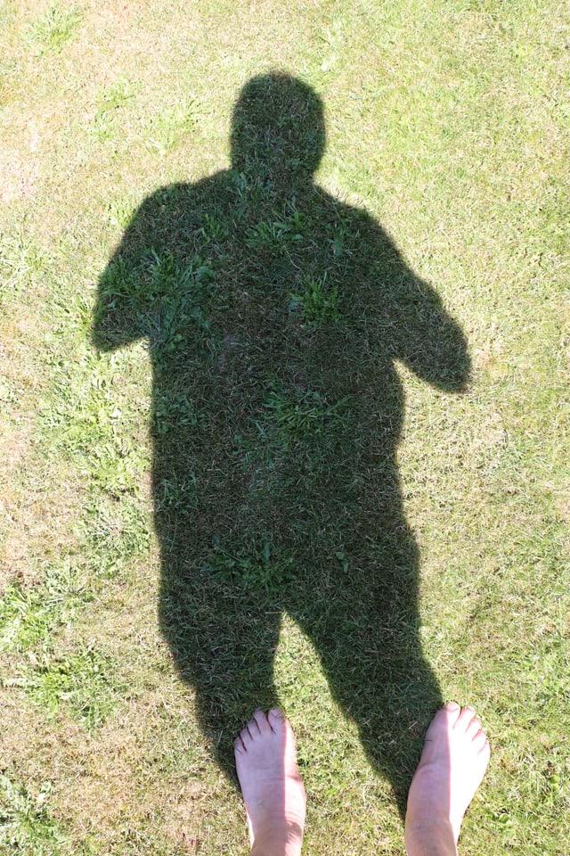 Bild mit echten Füssen und ganzem Schatten eines Fotographen.