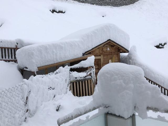 Viel Neuschnee auf einem Haus.