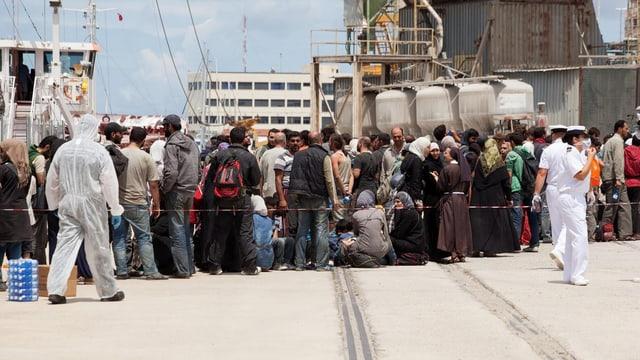 Flüchtlinge bei der Ankunft in einem Hafen.