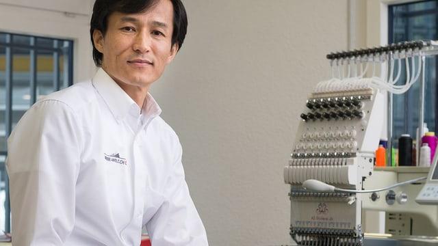 Ein Mann in weissem Hemd steht neben einer Maschine, über die sich Fäden spannen.