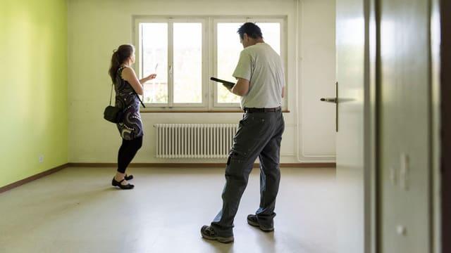 Eine Mieterin und ein Vermieter in einer leeren Wohnung.