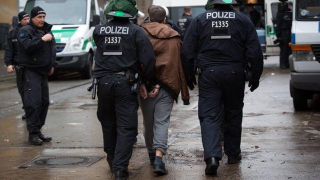Polizisten führen Mann in Handschellen ab