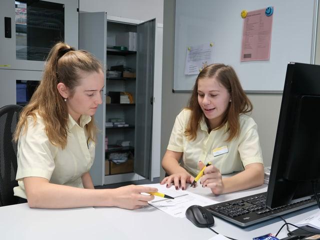 Zwei junge Frauen an einem Tisch in einer Besprechung.