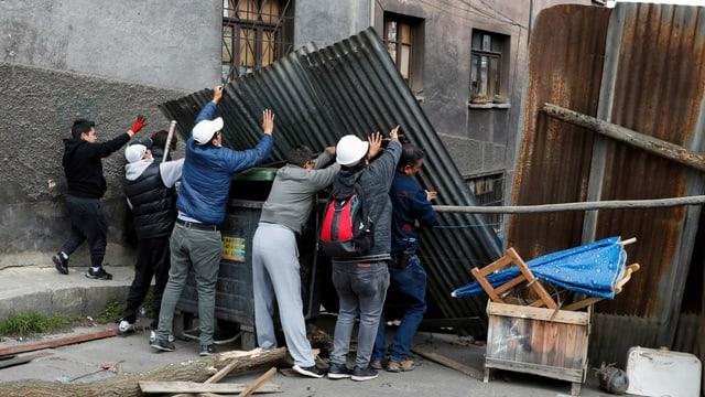 Mehrere Personen erstellen eine Wand aus Wellblech in einer Strasse.