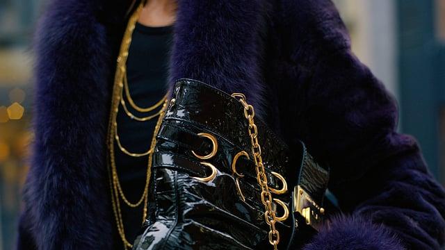 Frau mit Goldketten und Pelzmantel.