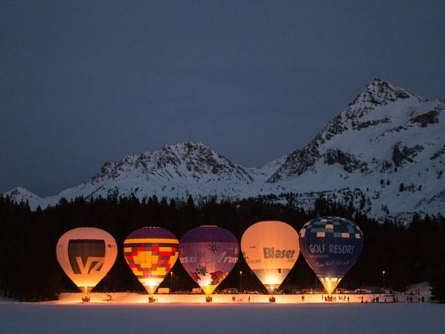 Feuernde Ballone stehen am Boden in verschneiter Landschaft.