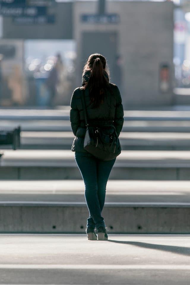 Eine Frau wartet am Zürcher Hauptbahnhof auf den Zug.