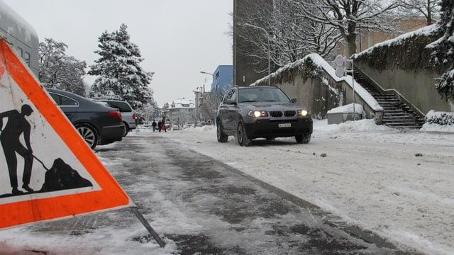 Eine Strasse mit Schnee, darauf ein Auto.
