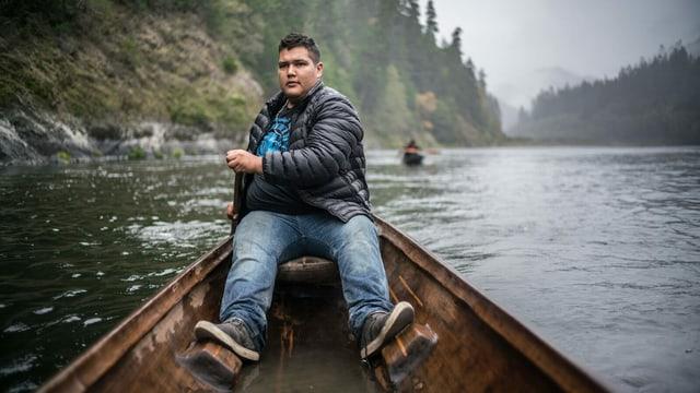 Ein junger Mann sitzt in einem Kanu auf einem Fluss.