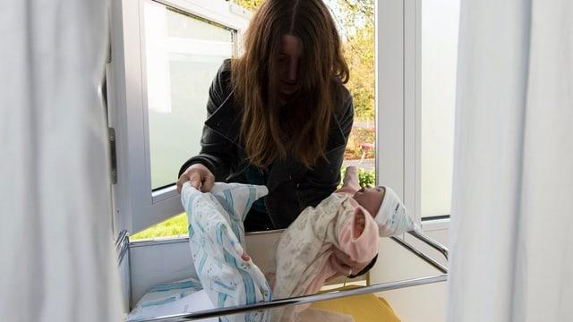 Eine Frau legt eine Puppe ins Babyfenster