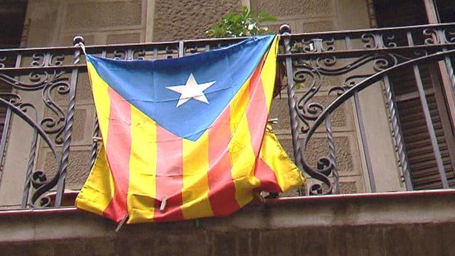 Die Unabhängigkeitsflagge der Region Katalonien weht an einem Balkongeländer in einer Gasse Barcelonas.