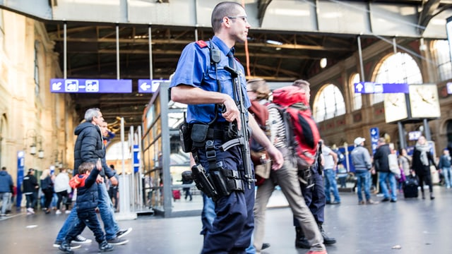 Bwaffneter Polizist patroulliert in der Halle des Zürcher Hauptbahnhofs