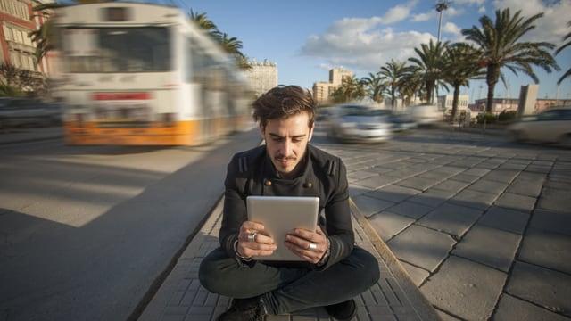 Junger Mann liest auf seinem iPad mitten auf der Strasse.