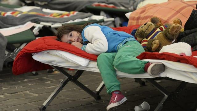 Ein Mädchen liegt auf einem Feldbett
