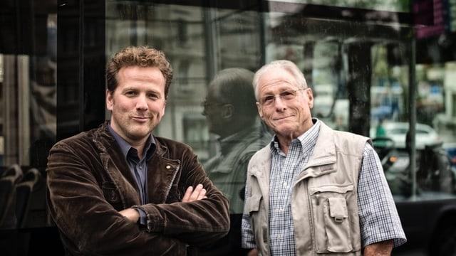 Christian Jott Jenny mit Jürg Randegger posieren vor einer Fensterscheibe.