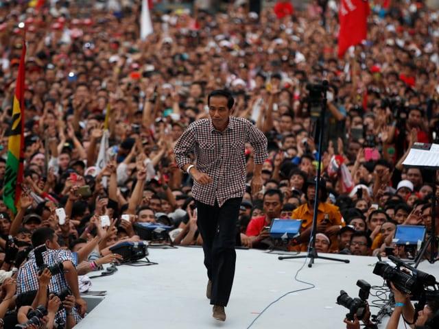 Joko Widodo läuft auf einer Bühne vor Publikum