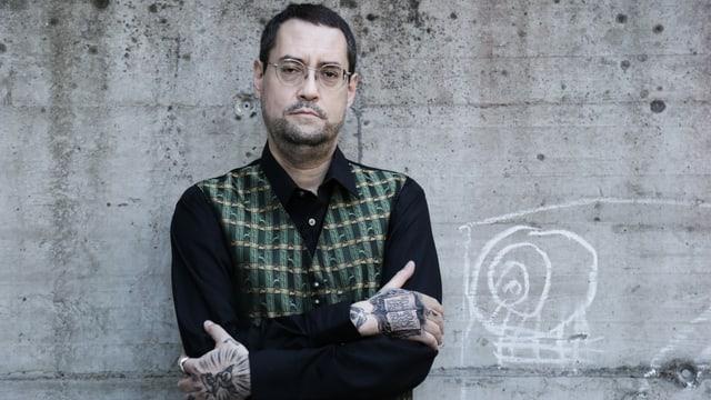 ein Mann mit vielen Tattoos an den Händen steht vor einer grauen Wand