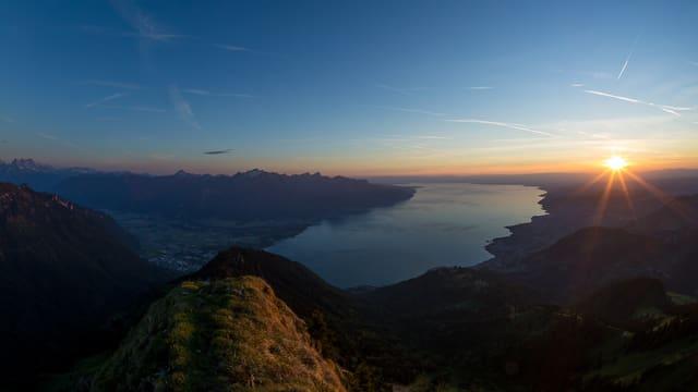 Blick von einem Berg auf den Sonnenuntergang und einen See.